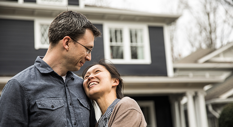Couple standing in front of home