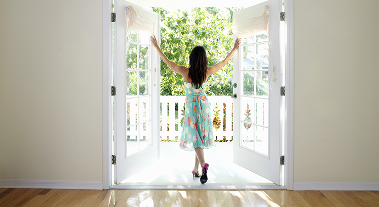 Woman standing in doorway with arms stretched out, rear view